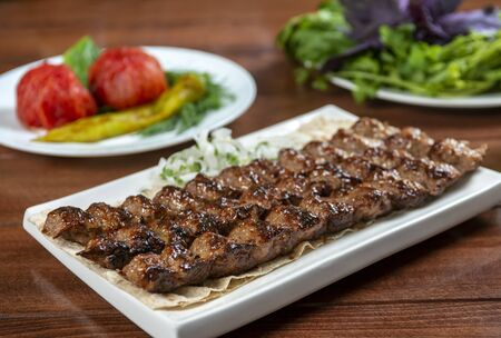 Fast food. Eastern food. Shish kebab, lyulya-kebab. Dishes of oriental cuisine lying in plte and decorated with greens and vegetables, sauces Reklamní fotografie
