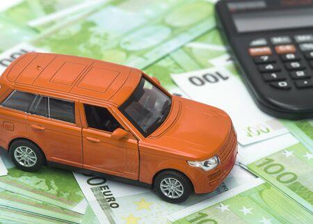 orange Auto und Geld, Euro und Dollar. Versicherungskonzept