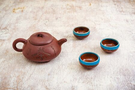 Brown clay teapot and cups on light wooden
