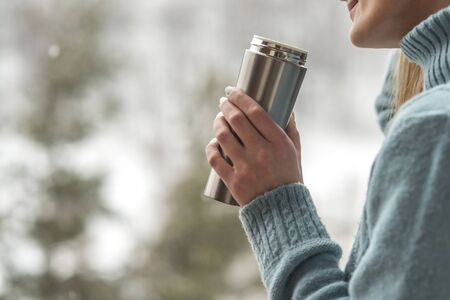 Woman in the background of a winter forest in a thermos bottle in hands