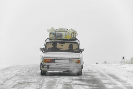 old passenger car loaded with goods on winter road