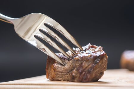 piece of meat on a fork, dark background Stock fotó