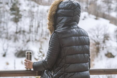 A girl in a winter jacket with a thermos of coffee or tea in her hand on the balcony in winter Stock fotó