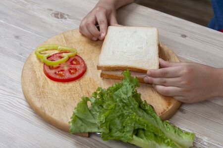 A boy is  preparing a sandwich of meat and vegetables. Breakfast for school.