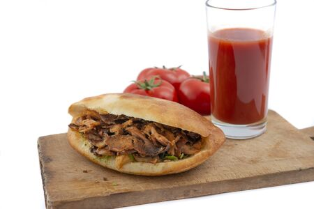 shawarma in pita bread ,tomatoes and tomato juice on a white background.doner kebab