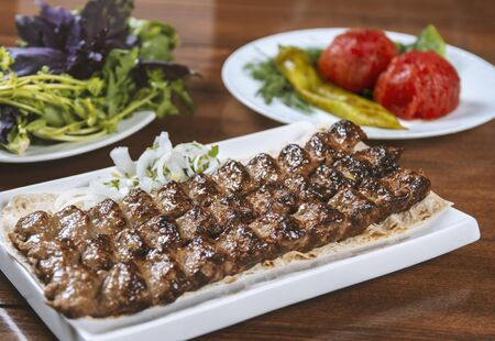 Fast food. Eastern food. Shish kebab, lyulya-kebab. Dishes of oriental cuisine lying in plte and decorated with greens and vegetables, sauces Stock fotó
