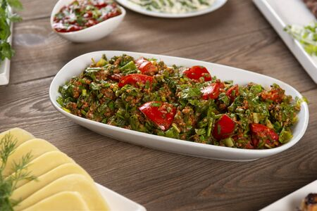 Tabbouleh salad with bulgur, tomatoes, parsley and green onion in plate on wooden table. Traditional middle eastern or arab dish. Stock fotó