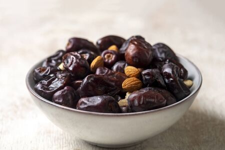 Mix of dates and nuts in plate on a white wood background .healthy food