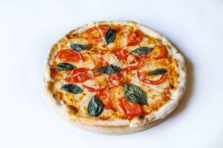 Sabrosa pizza de verduras en el tablero del escritorio sobre fondo blanco. Foto de archivo