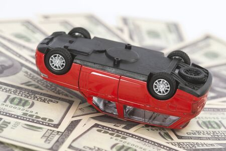 toy, red car had accident on dollar banknotes.insurance concept Фото со стока