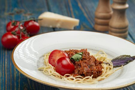 Tasty spaghetti with minced meat and cherry tomatoes on blue wooden background.