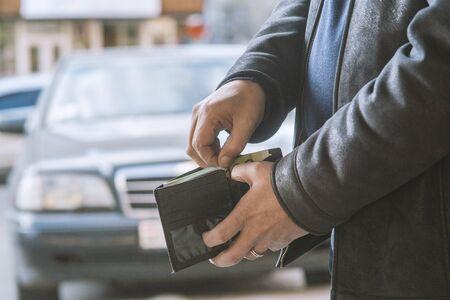 man pulls money out of his wallet Banco de Imagens