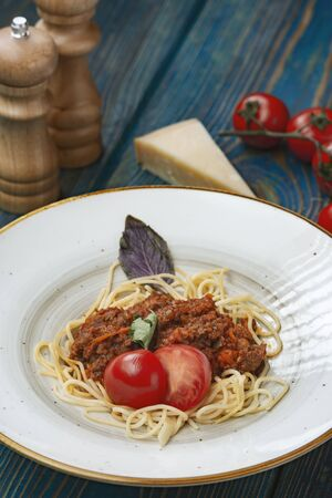 italian Pasta bolognese with meat, tomato sauce and vegetables in blue wooden desk .
