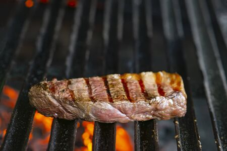 grilling steaks on flaming grill and shot with selective focus Stock fotó