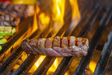 Asar bistecs a la parrilla en llamas y rodar con enfoque selectivo