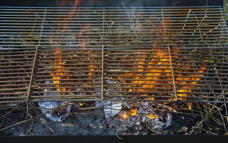 Freshly lit barbecue fire with logs of burning wood over small chips of kindling in a portable BBQ Standard-Bild - 140190733