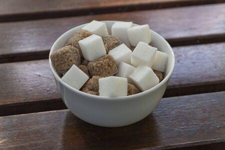 Cubes de sucre blanc et brun dans un bol sur une table en bois Banque d'images