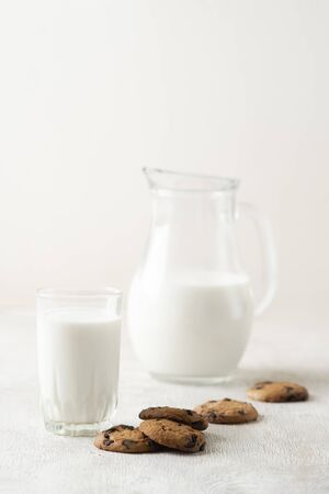 Milk in a jug and chocolate chip cookies on on a white wooden background copy space. Standard-Bild