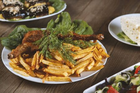 roasted chicken and french fries on a wooden table