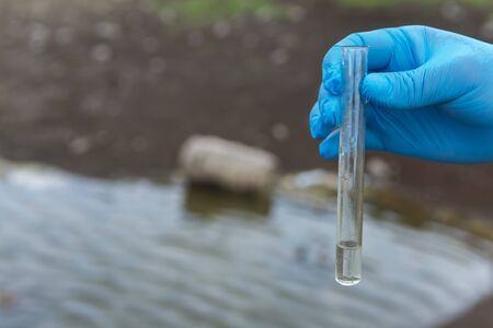 A water sample from the river. Hand in glove collects water in a test tube. ecology concept Standard-Bild