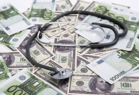 Medical stethoscope on dollars and euro banknotes.