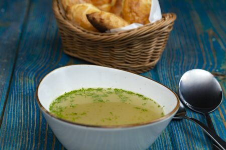 chicken broth in white bowl and baked pies in a basket on blue wooden desk Standard-Bild
