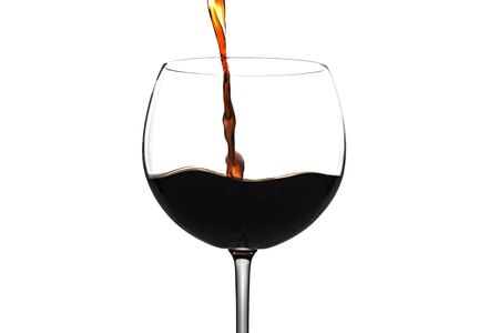 Pouring red wine glass over a white Standard-Bild