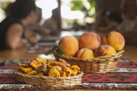 Dried fruts and Fresh peaches fruits with leaves in basket on rustic background Standard-Bild