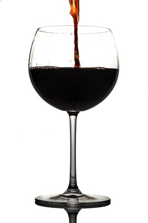 Red wine being poured into wine glass on white