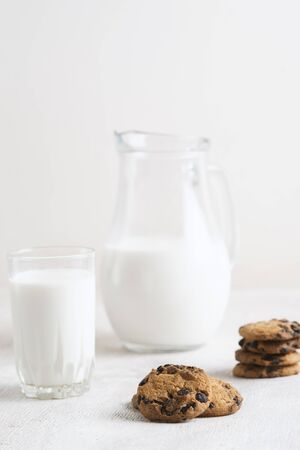 chocolate chip cookies and milk in a jug and a glass on a white wooden  background Standard-Bild