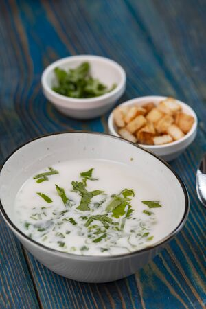 yogurt soup with herbs and crackers on a blue wooden table