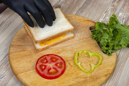 A man prepares lunch, serves a sandwich with bread on a wooden cutting board, with green salad, cheese and sausage