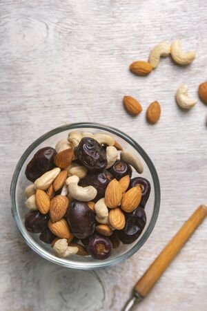 Mix of dates and nuts in plate on a white wood background .Top view.healthy food