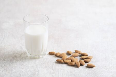 Healthy vegan nut milk and almonds on white wooden background. Selective focus, space for text.
