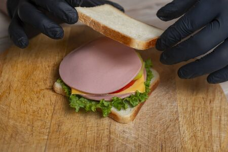 man in black gloves prepare sandwich on wooden desk