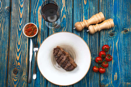 Sirloin steak and cherry tomatoes on a plate with wine. View from above