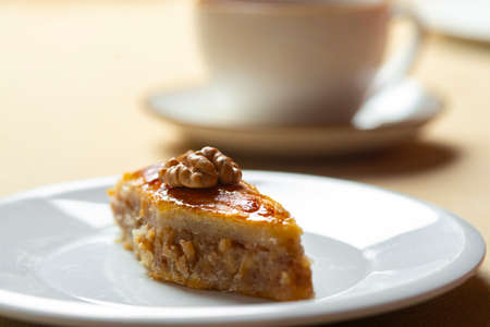 Traditional arabic dessert baklava and walnuts in white plate with a cup of coffee or tea. Homemade baklava with nuts and honey.