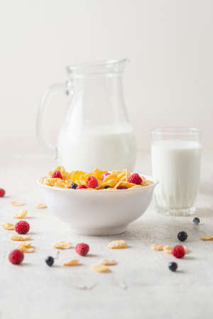 Corn Flakes with berries raspberries, blueberries and currants with milk on white wooden background