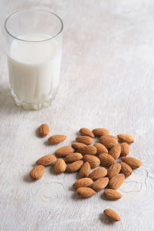 Vegan dairy free almond milk and almonds on white wooden background. Selective focus, space for text.