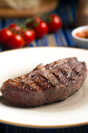 Roasted steak, cherry tomatoes, salt and pepper on blue wooden table. Banque d'images