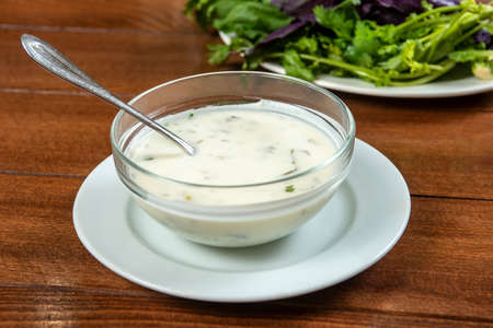 yogurt soup with herbs in a plate on a wooden table.spas