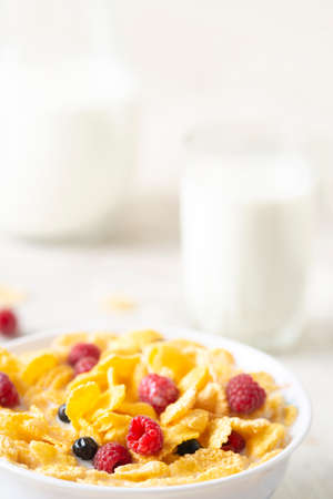 bowl of corn granola with milk, fresh raspberries, blueberries. milk in a jug and a glass on white wooden board for healthy breakfast Banque d'images