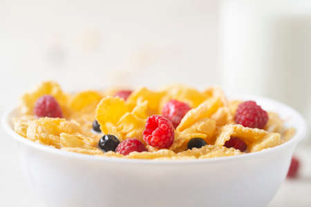 Healthy breakfast with cereal and blueberry and raspberry. Bowl with healthy cornflakes, milk and berries. Tasty circle cornflakes.oatmeal with fruits. Diet concept. Close up