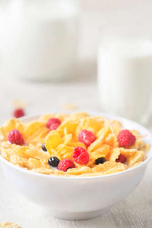 Healthy breakfast with cereal and blueberry and raspberry. Bowl with healthy cornflakes, milk and berries on white table. Tasty circle cornflakes.oatmeal with fruits. Diet concept.