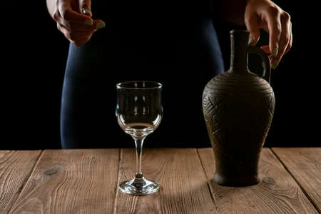 jug with wine and a glass on a wooden table Foto de archivo