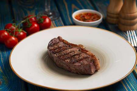 Grilled steak, cherry tomatoes salt and pepper on wooden table.