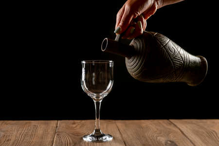 girl hands pouring red wine into a glass from a clay bottle on a black background