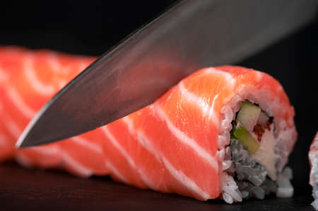 Preparing sushi at home - close up of hands cutting a Roll on a board.
