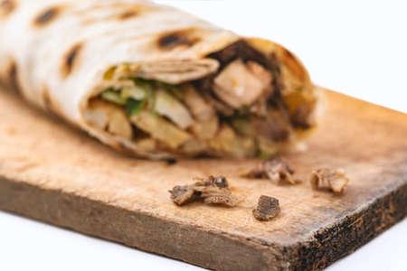 Doner Kebab Gyros Shawarma beef or chiken roll in pitta bread sandwich on wooden desk