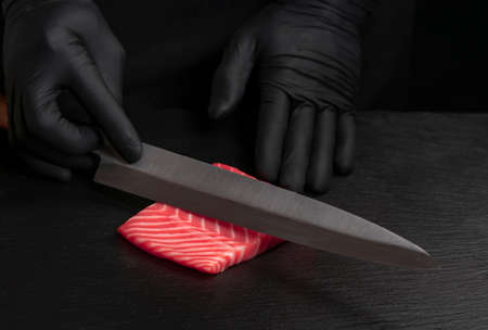 Chef cut fresh red salmon fish with sharp knife on black board. He is working on sashimi. Preparing traditional japanese sushi set. Only hands close up Stock fotó - 157776508